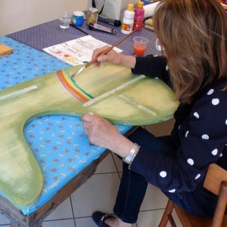 Officina del Legno: una signora dipinge Girandolo per il nipotino